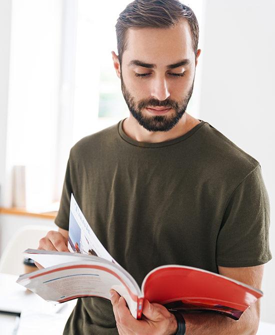 Junger Mann informiert sich in Zeitschrift über das Thema IT Business Management | ©Drobot Dean | AdobeStock 301956916