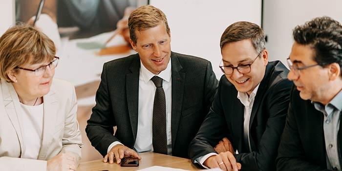 Vier Mitarbeiter*innen sprechen über Enterprise Service Management an Meeting-Tisch ©agineo