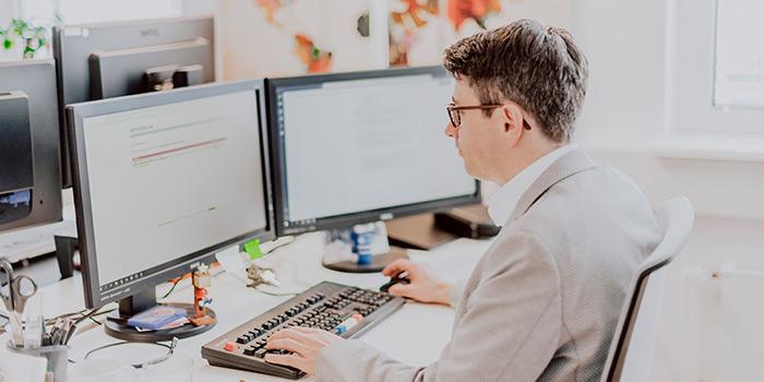 agineo-Mitarbeiter sitzt konzentriert am Laptop ©agineo