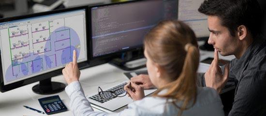 Zwei Mitarbeiter am Bildschirm beschäftigen sich mit der Configuration Management Database AixBOMS ©REDPIXEL | AdobeStock 143605968