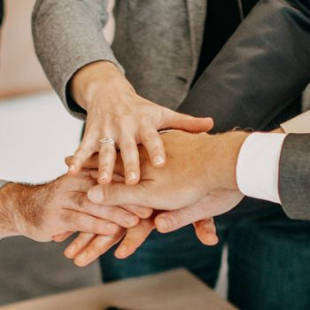 Mehrere Hände liegen aufeinander im Team-Meeting. ©agineo